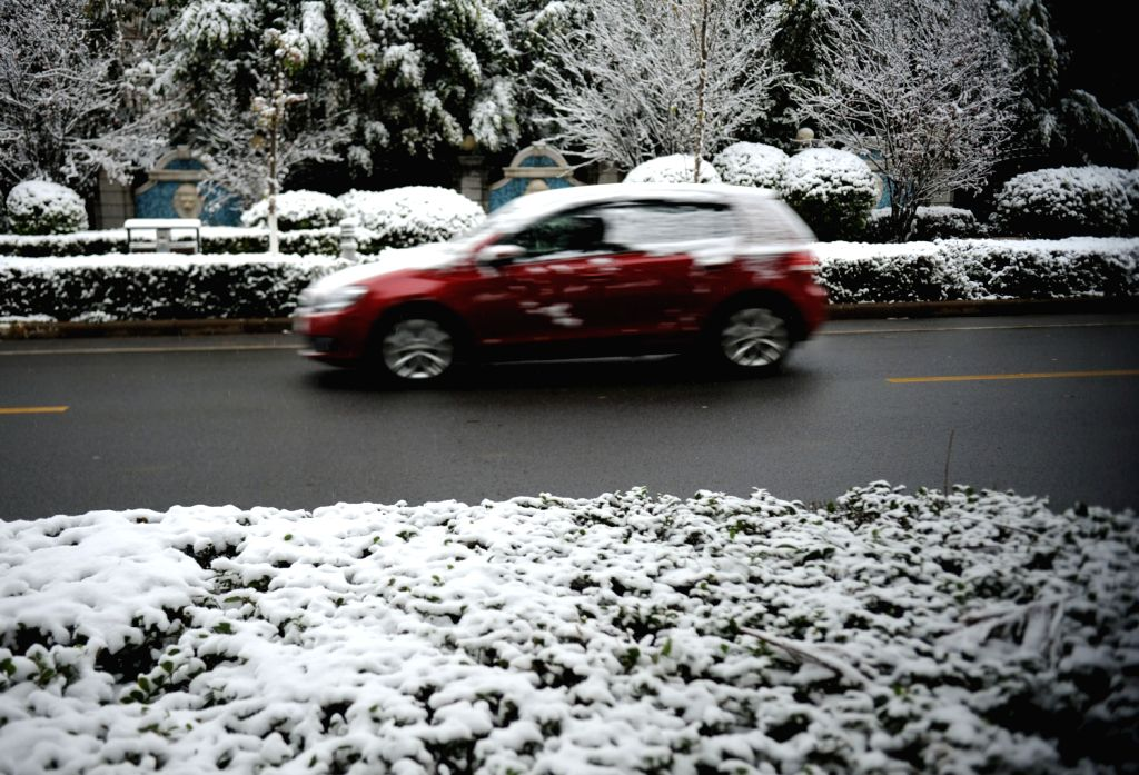 A car runs on a snowy road in Kunming, capital of southwest China's Yunnan Province, Dec. 16, 2013. Kunming, the Spring City, witnessed a snowfall from ...