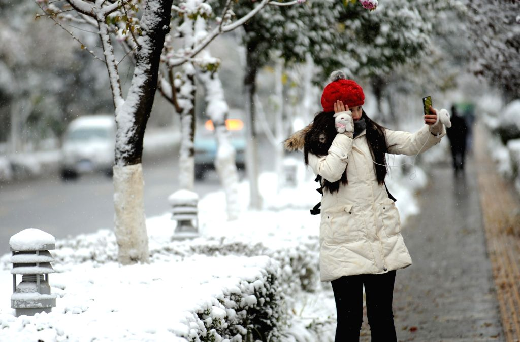 A woman takes a selfie on a snow-covered paveway in Kunming, capital of southwest China's Yunnan Province, Dec. 16, 2013. Kunming, the Spring City, ...