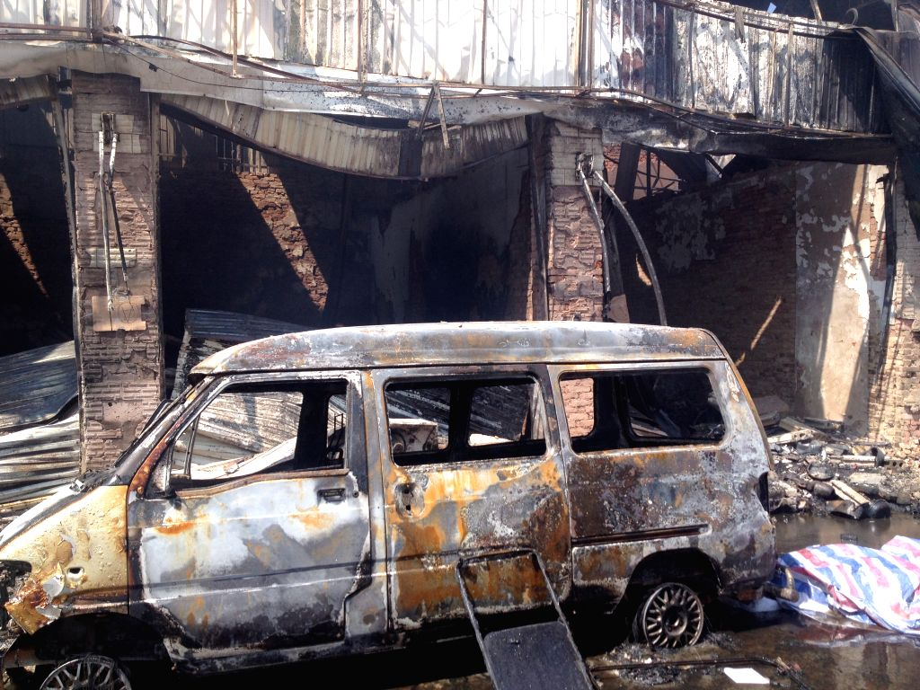 A burnt vehicle is seen in this picture taken with a cellphone at the Dongmeng Lianfeng Agricultral Trade Center in the Guandu District of Kunming, capital of ...