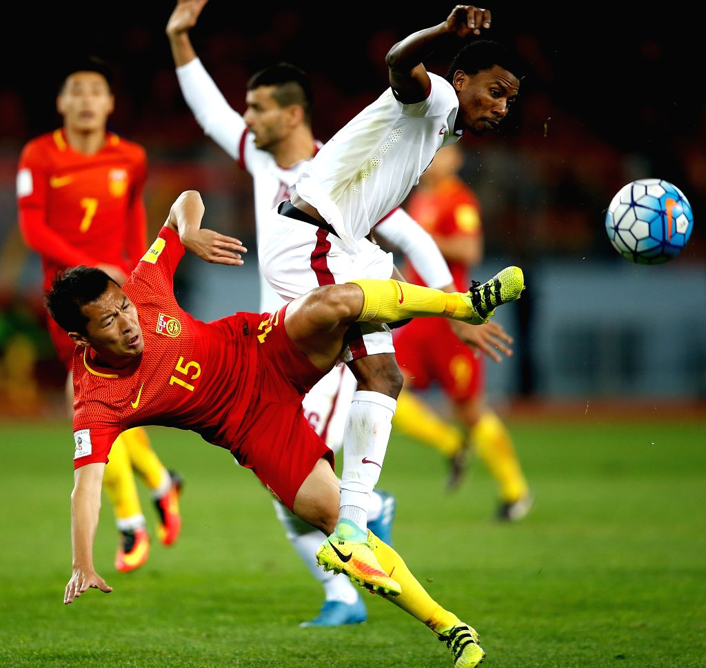KUNMING, Nov. 15, 2016 - China's Wu Xi (front L) vies with Qatar's Mohammed Kasoala during the Russia 2018 FIFA World Cup qualification match in Kunming, southwest China's Yunnan Province, Nov. 15, ...