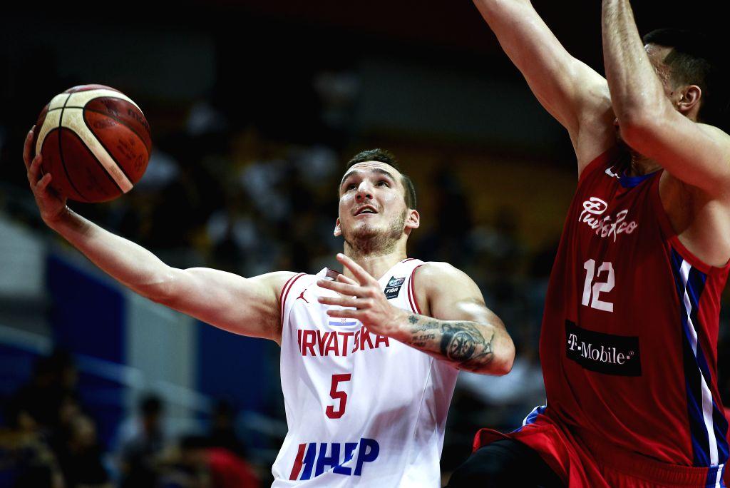 KUNSHAN, Aug. 11, 2019 - Jordano Antonio (L) of Croatia goes for a basket during a match against Puerto Rica at the 2019 International Men's Basketball Challenge in Kunshan, east China's Jiangsu ...