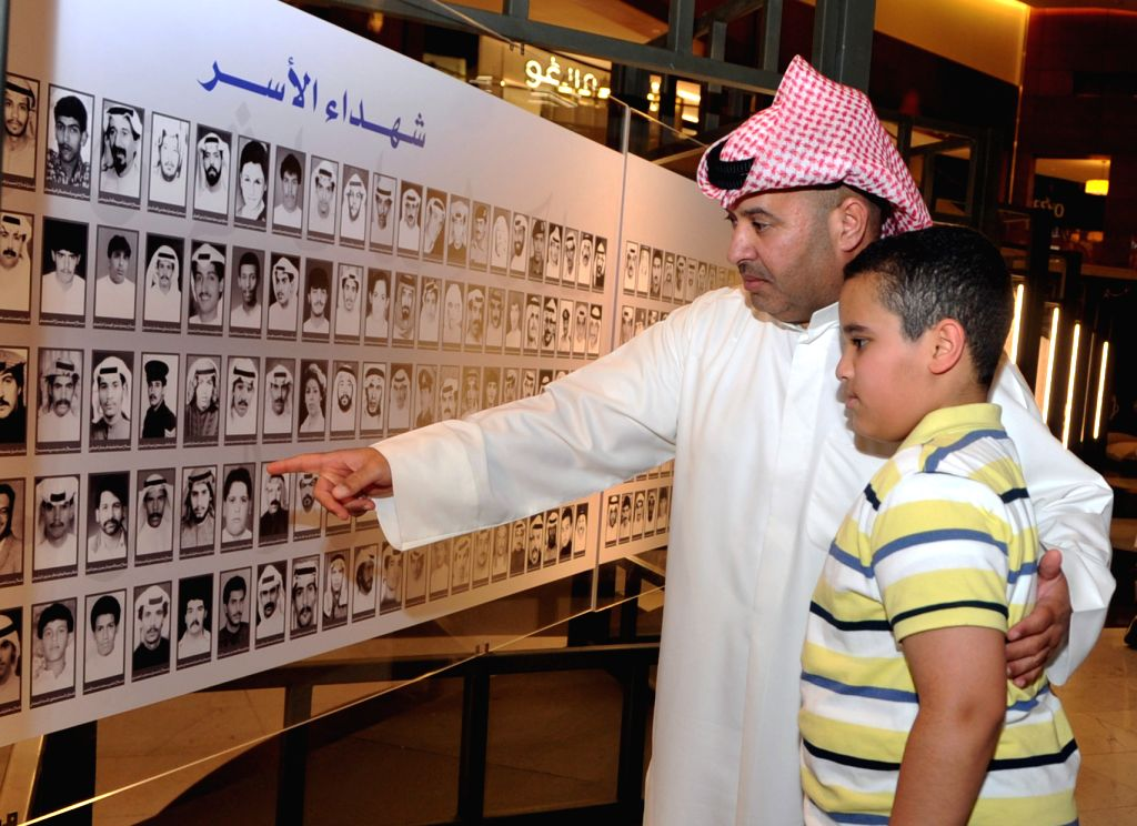 KUWAIT CITY, Aug. 1, 2019 - A father and his son view pictures of Kuwaiti martyrs of the Gulf War in Kuwait city, Kuwait, Aug. 1, 2019. A special event was held on Thursday in Kuwait City on the ...