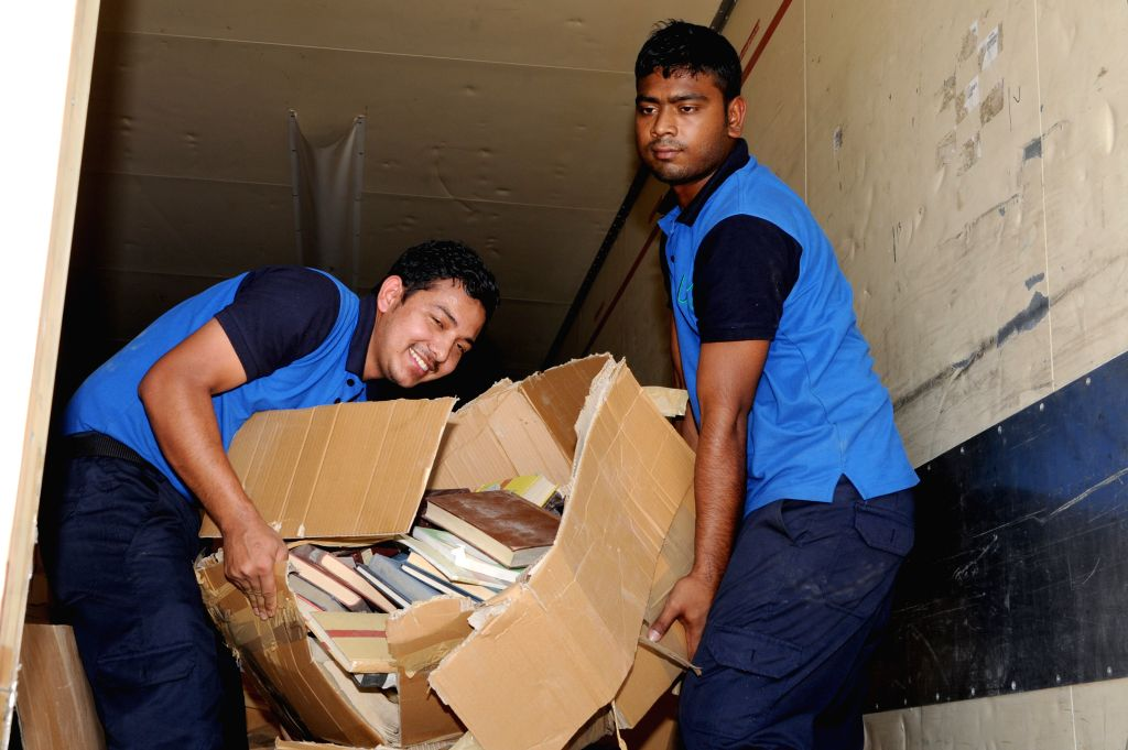 KUWAIT CITY, Aug. 28, 2019 - Workers transport books to a truck during a handover ceremony in Kuwait City, Kuwait, on Aug. 28, 2019. Iraq handed over on Wednesday 42,000 books to Kuwait which were ...