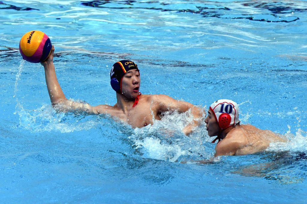 KUWAIT CITY, Dec. 13, 2019 - He Xingmeng (L) of China passes the ball during the preliminary match between China and Japan at the FINA World Men's Junior Water Polo Championships 2019 in Farwaniya ...