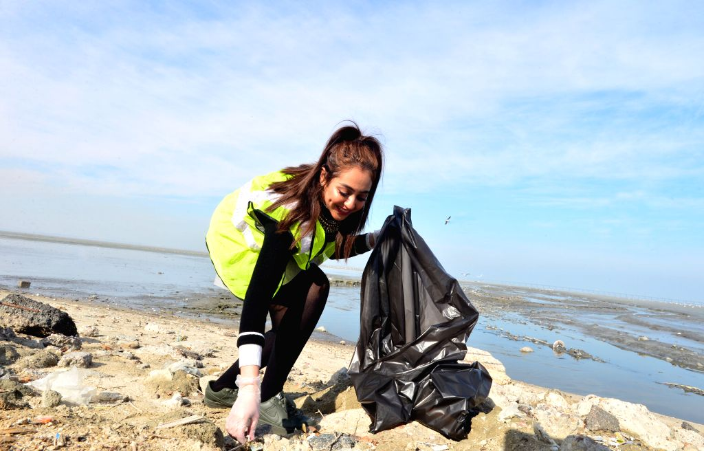 KUWAIT CITY, Dec. 14, 2019 - A woman participates in a beach cleaning campaign in Kuwait City, Kuwait, on Dec. 14, 2019. Kuwait Institute for Scientific Research (KISR) launched on Saturday a ...