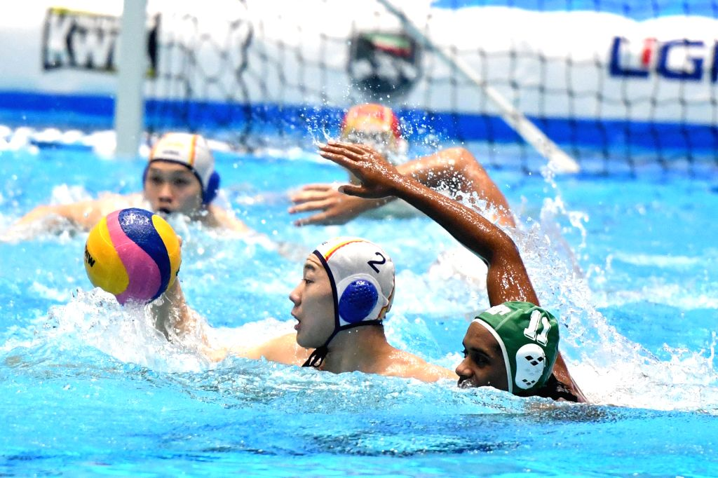 KUWAIT CITY, Dec. 14, 2019 - He Xingmeng (front L) of China vies with Yaseen Magro of South Africa during the preliminary match between China and South Africa at the FINA World Men's Junior Water ...