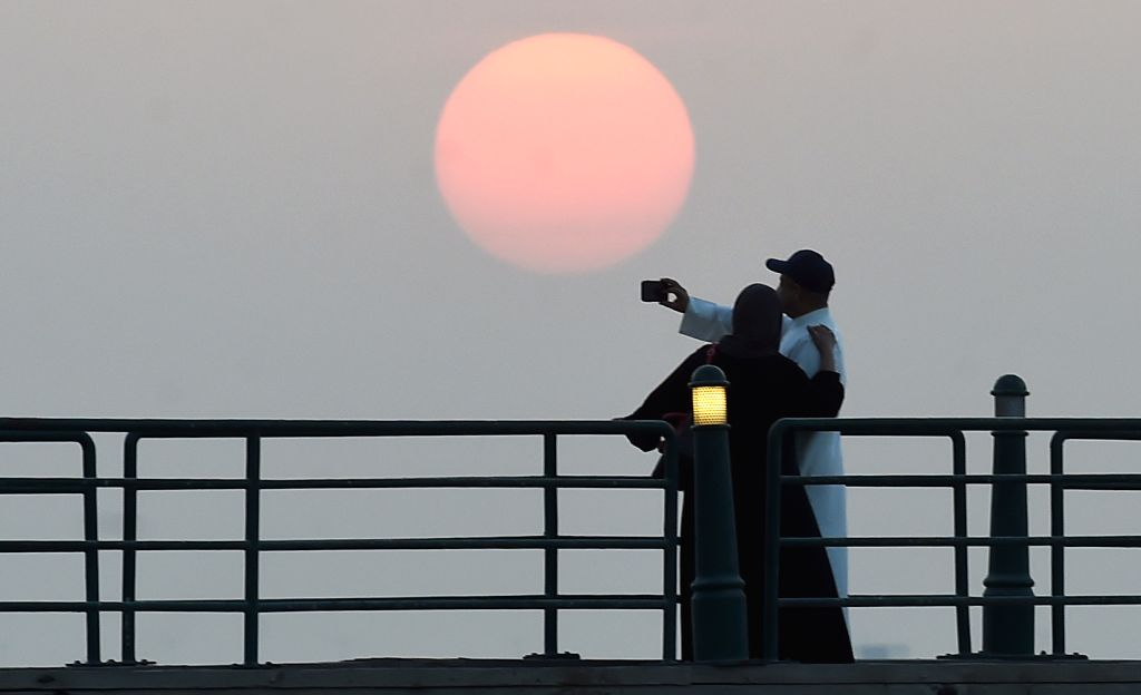 KUWAIT CITY, Sept. 16, 2019 - Local people take a picture on a bridge at the seaside during sunset in Kuwait City, Kuwait, on Sept. 15, 2019.