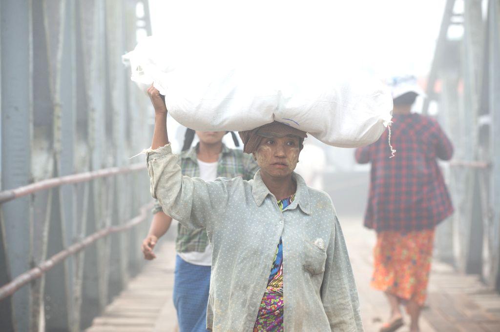 KYAUKPYU, Jan. 14, 2020 (Xinhua) -- Female laborers unload goods from cargo ship at a pier in Kyaukpyu, Rakhine State, Myanmar, Jan. 13, 2020. (Xinhua/Du Yu/IANS)