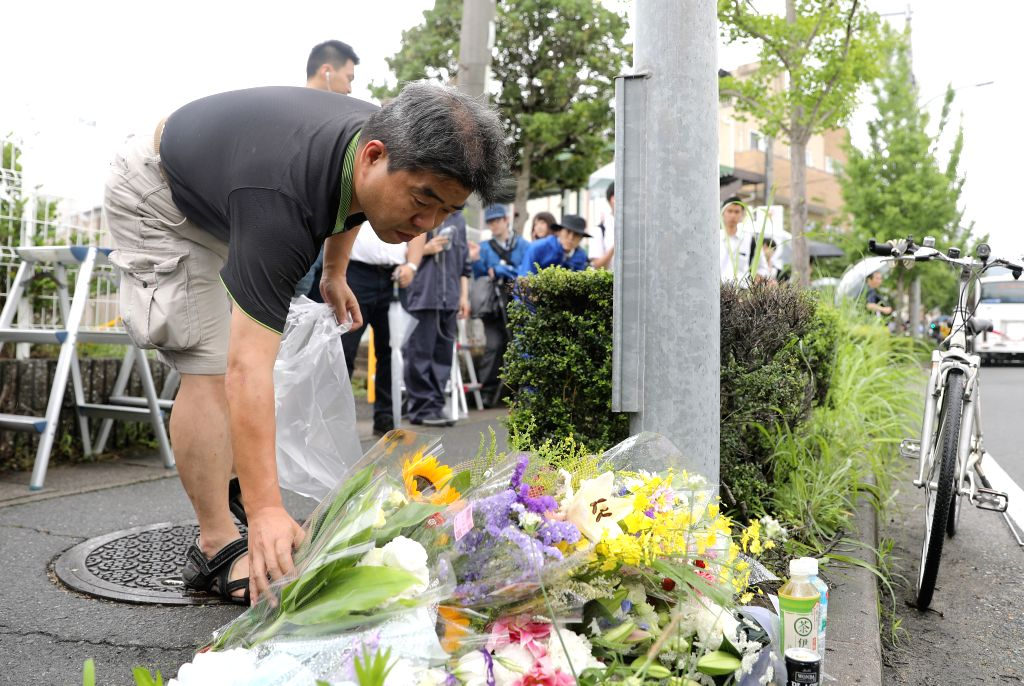 KYOTO, July 19, 2019 - A man lays flowers near the site of an arson attack in Kyoto, Japan, July 19, 2019. Industry insiders from Japan's animation scene along with countless numbers of fans ...