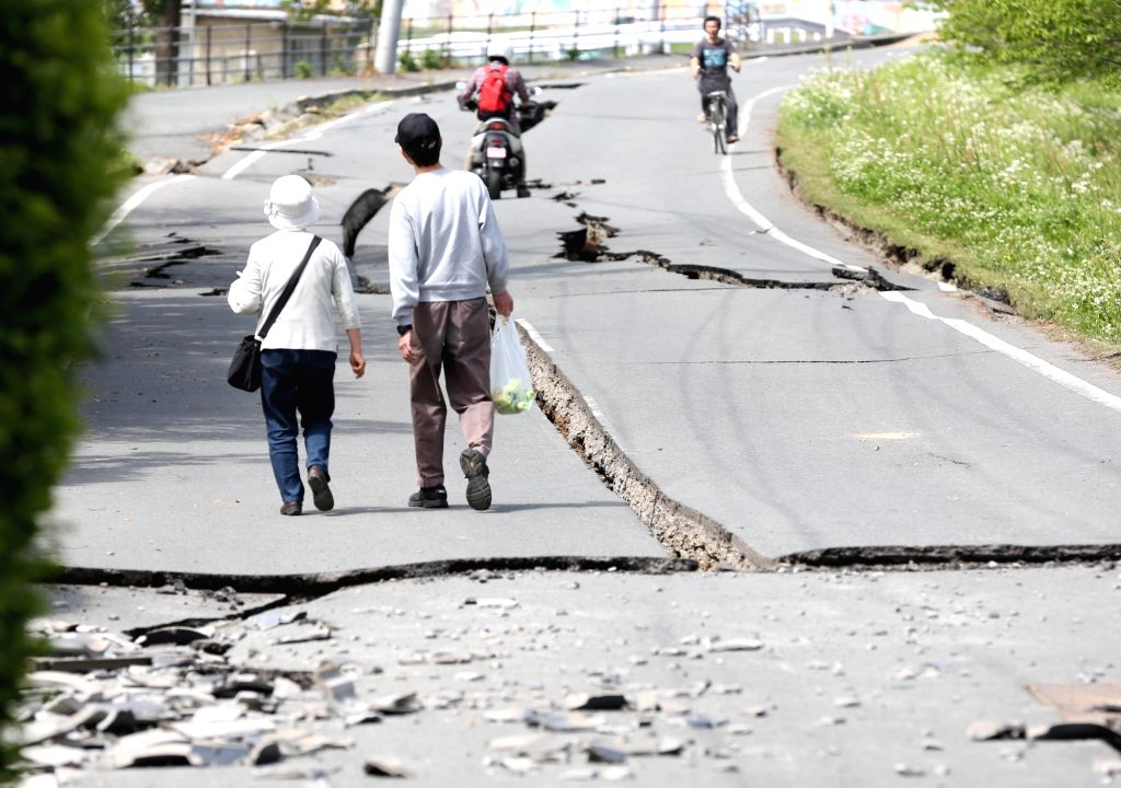 Kyushu (Japan): People walking on a street damaged by an earthquake. According to Japanese media reports, at least 15 people were killed and 760 injured as a powerful earthquake measuring 7.3 on the ...