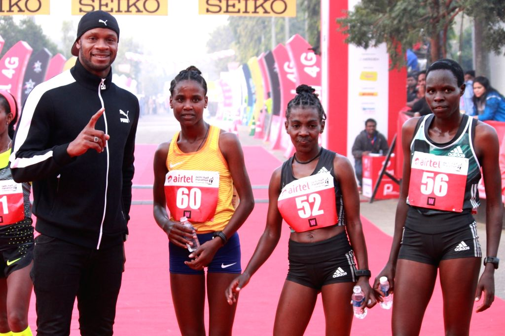 (L to R) Ethiopia's Ababel Yeshaneh (2nd place), Ethiopia's Worknesh Degefa (1st place) and Kenyan Helah Kiprop (3rd place) winners of the women's race with Jamaican sprinter Asafa Powell ...