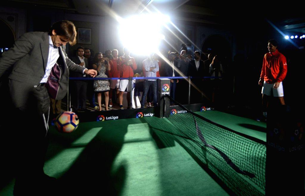 La Liga ambassador, former Real Madrid and Liverpool striker Fernando Morientes plays football with Spanish tennis player Rafael Nadal at the launch of La Liga in India, in New Delhi on ...