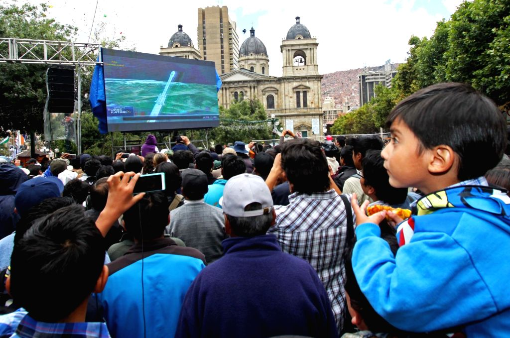 People gather to watch the launch in China of the first Bolivian telecommunications satellite, Tupac Katari, at the Murillo Square in La Paz, capital of ...