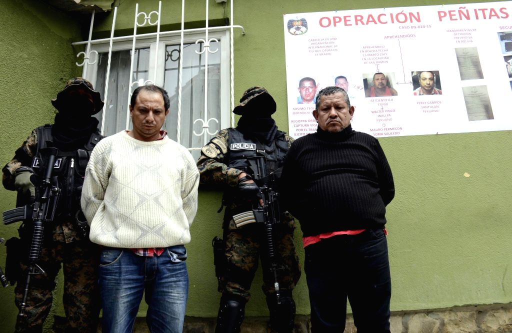 Members of the Special Force of Fight Against Drug Trafficking (FELCN) of Bolivia and the Drug Enforcement Directorate of Peru escort two alleged drug traffickers ...