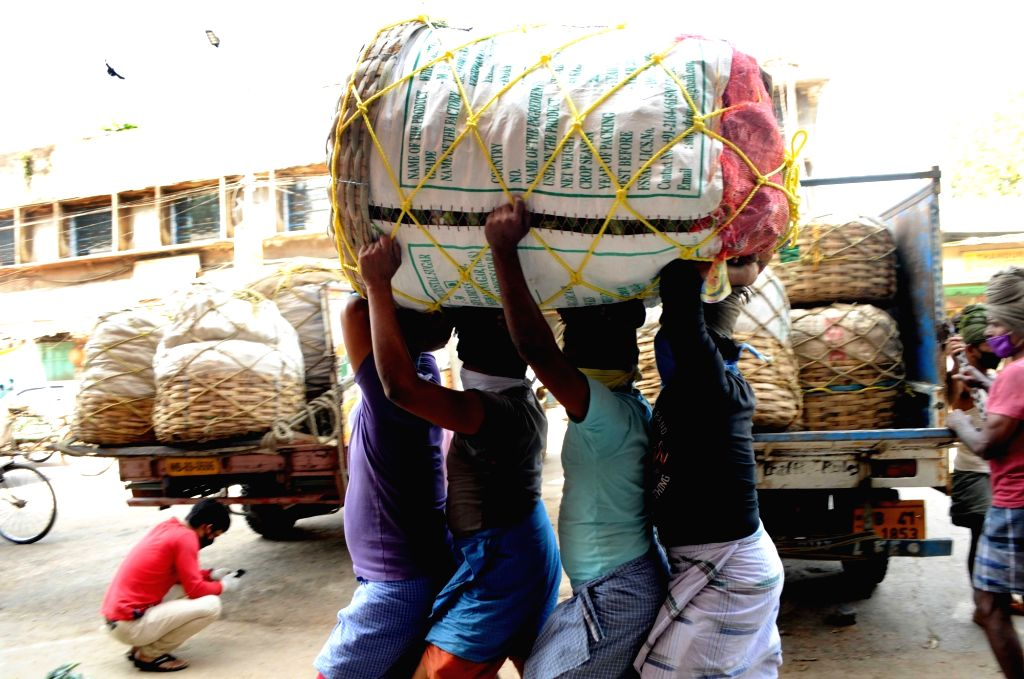 Laborers carry a sack of essential commodities on their heads on Day 6 of the 21-day countrywide lockdown imposed to contain the spread of novel coronavirus, in Kolkata on March 30, 2020.