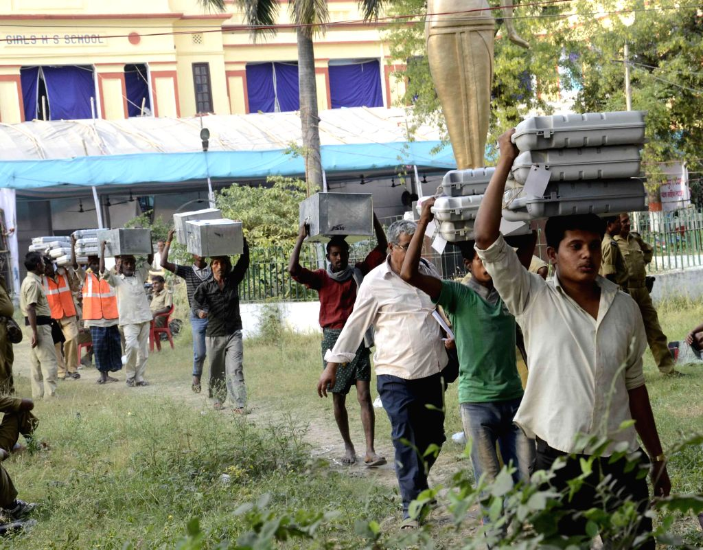 Laborers carry Electronic Voting Machines (EVMs) as Polling personnel leave for their respective polling booths ahead of the 5th phase of 2014 Lok Sabha Elections from a polling station in Patna on ..