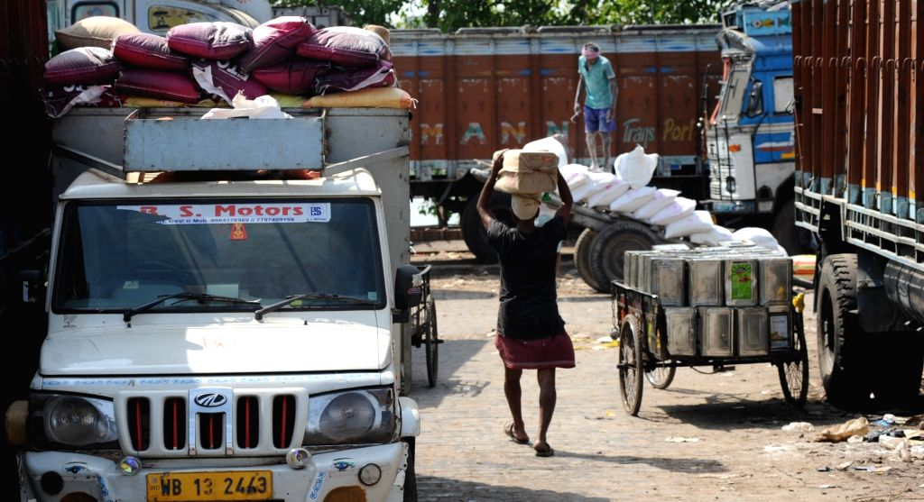 Laborers engaged in the supply and transportation of essential commodities at Posta Bazar on Day 7 of the 21-day nationwide lockdown imposed as a measure to contain the spread of  ...