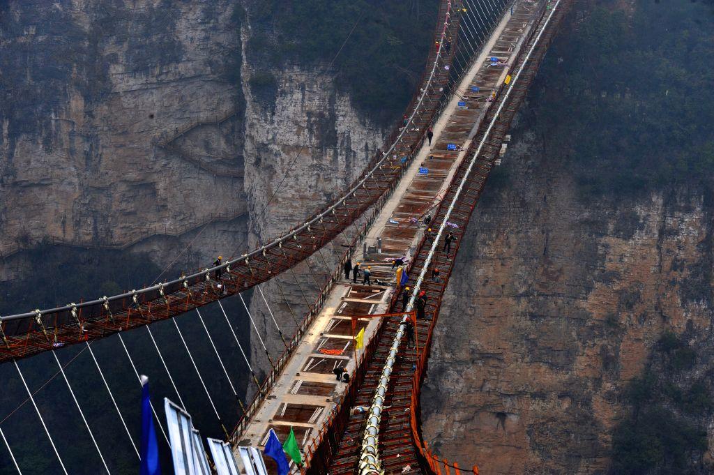 Laborers work on the glass bridge across the Zhangjiajie Grand Canyon in Zhangjiajie, central China's Hunan Province, Jan. 18, 2016. The bridge is 430 meters ...