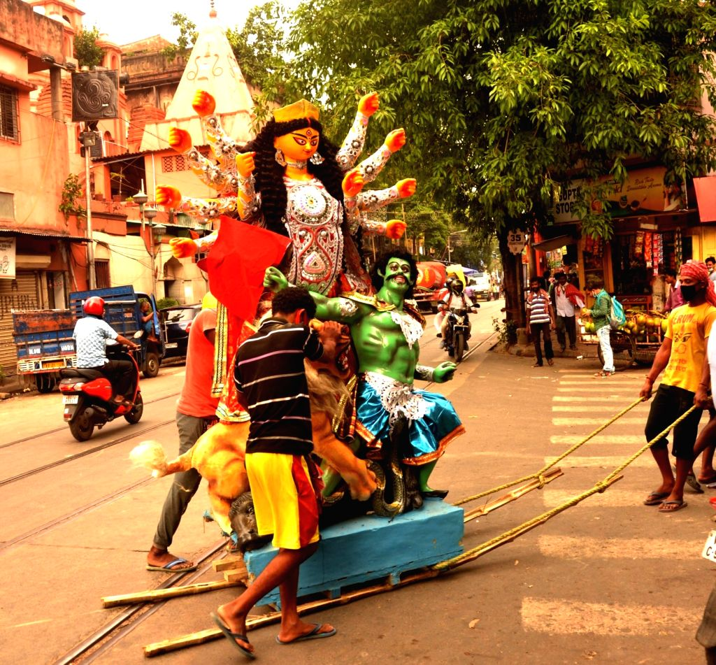 Labour carrying an Idol of Goddess Durga on their way to the community Puja pandal ahead of Durga Puja festival in Kolkata on October 18, 2020.