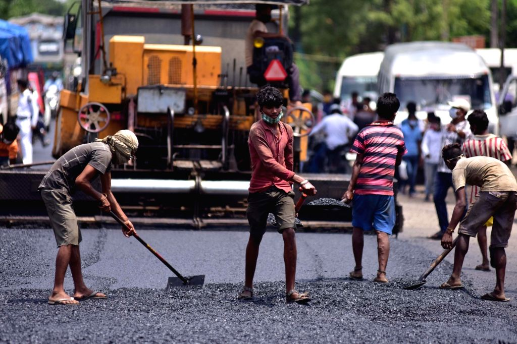 Labourers busy working at a road construction site in Assam's Nagaon after certain restrictions were relaxed by the state authorities during the extended nationwide lockdown imposed to ...