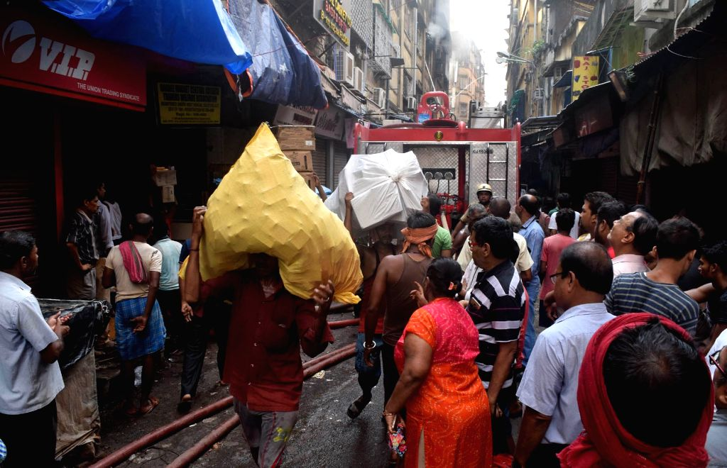 Labourers carry goods to safe place from Bagri Market where a massive fire broke out yesterday; in Kolkata on Sept 16, 2018.