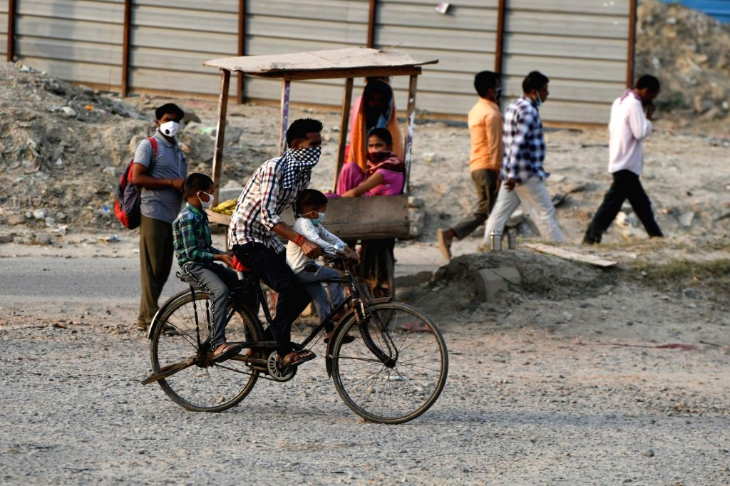 Labourers riding a cycle on their way back home after completing their work during the extended nationwide lockdown imposed to mitigate the spread of coronavirus, in Noida on May 9, 2020.