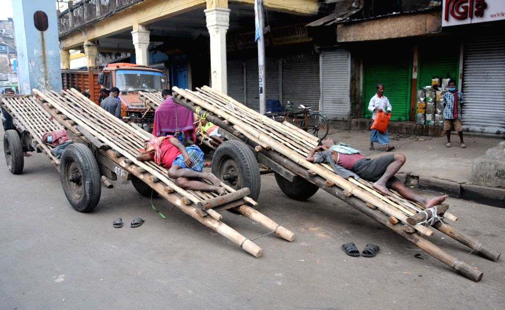 Labourers seen resting outside a wholesale market amid protests during the 24-hour nationwide trade union strike called by the central trade unions against the central government's new farm ...