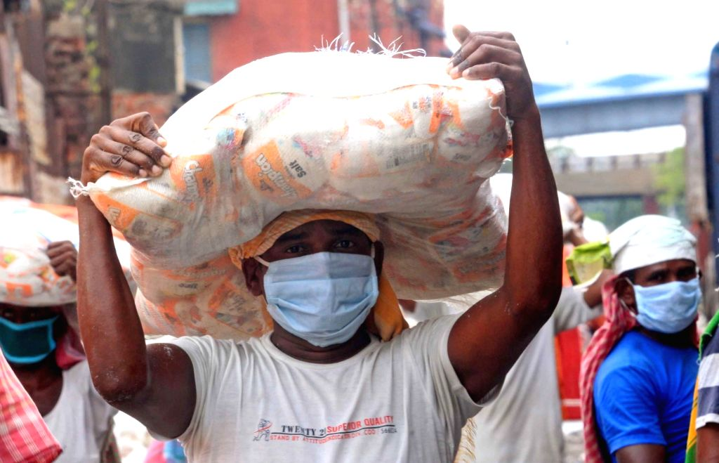 Labourers unload sacks of foodgrains from the wagons of a freight train at Chitpur in Kolkata during the extended nationwide lockdown imposed to mitigate the spread of coronavirus; on Apr ...