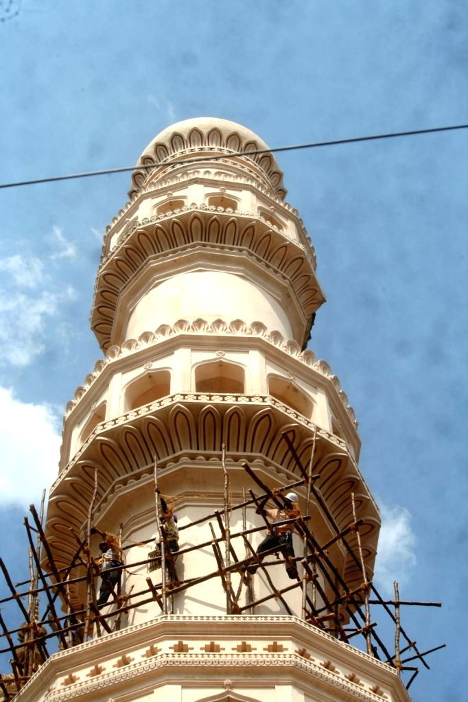 Labours busy working, where a portion of lime stucco work on one of the minarets of Charminar fell down following unseasonal rains, in Hyderabad on May 5, 2019.