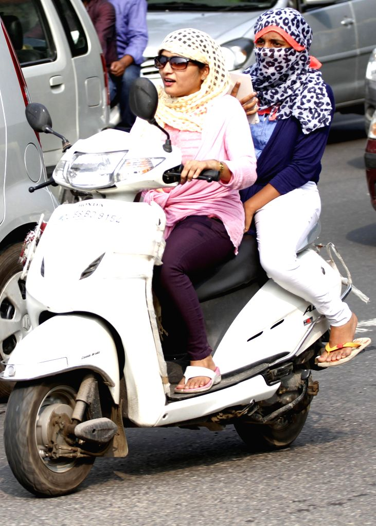 Ladies ride on Delhi roads without wearing helmets defying Delhi government's notification which has made wearing of helmets mandatory for women, on Aug 29, 2014.