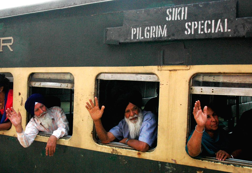 Indian Sikh pilgrims wave as they arrive at Wagah Railway Station in eastern Pakistan's Lahore on April 11, 2015. The first batch of Sikh pilgrims arrived in ...