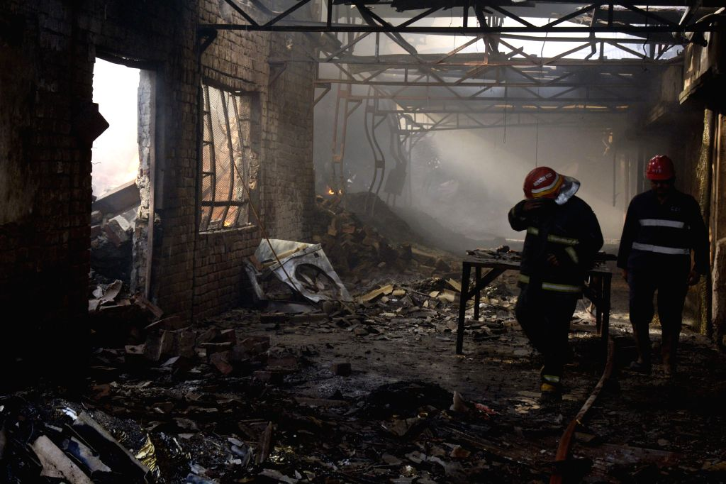 LAHORE, April 21, 2016 - Fire fighters examine the fire site at a foam factory in eastern Pakistan's Lahore on April 21, 2016. At least three workers were injured on Thursday as hug fire erupts in ...