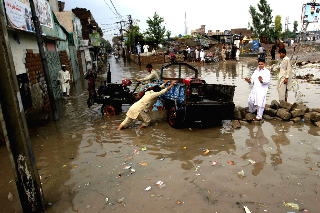 A man pushes a vehicle in a flooded area after heavy rain in northwest Pakistan's Peshawar, April 28, 2015. At least 30 people were killed and 150 others injured in ...
