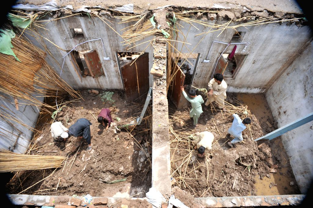 Residents examine their damaged homes after heavy rain in northwest Pakistan's Peshawar on April 28, 2015. At least 30 people were killed and 150 others injured in ...