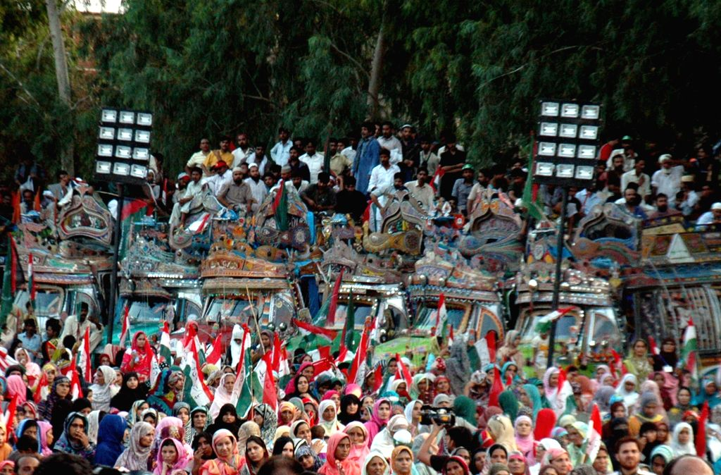 Pakistani supporters of religious leader Tahir-ul-Qadri gather outside his house in eastern Pakistan's Lahore on Aug.10, 2014. Pakistan Awami Tehreek (PAT) chief ...