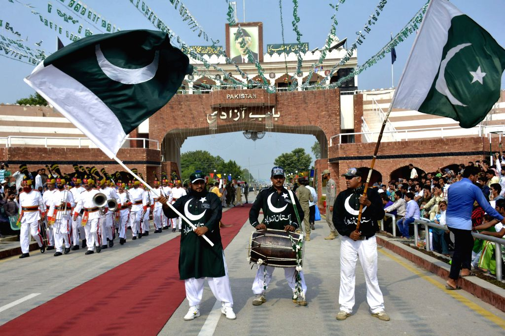 LAHORE, Aug. 14, 2016 - Pakistani people wave national flags during a ceremony celebrating Pakistan's 70th Independence Day at the Pakistan-India Wagah Border in eastern Pakistan's Lahore, Aug. 14, ...