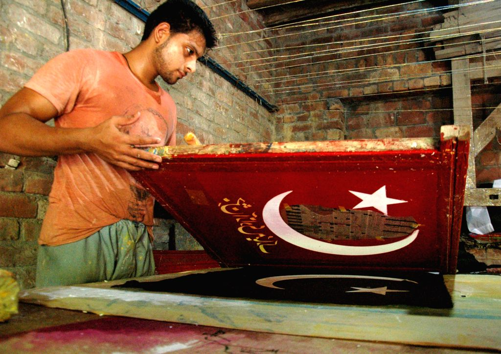 A Pakistani man prints Pakistan's national flag ahead of the country's independence day in eastern Pakistan's Lahore on Aug. 5, 2014.  ...