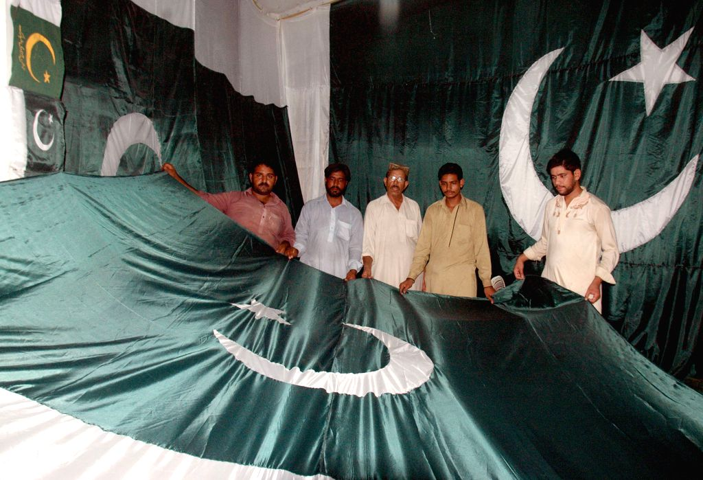Pakistani men hold a giant Pakistan's national flag in a printing factory ahead of the country's independence day in eastern Pakistan's Lahore on Aug. 5, 2014. ...