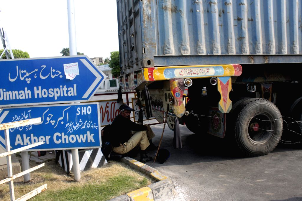 A Pakistani policeman rests as a container truck is placed to block the area near the house of religious scholar Tahir-ul-Qadri, ahead of upcoming anti-government ... - Nawaz Sharif and Imran Khan