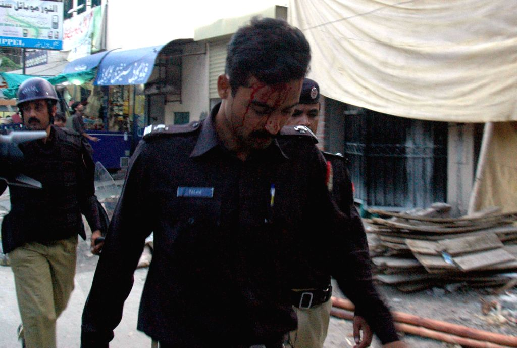 An injured policeman is seen after a clash in eastern Pakistan's Lahore on Aug. 8, 2014. Pakistan police used tear gas shells to disperse anti-government protesters ..