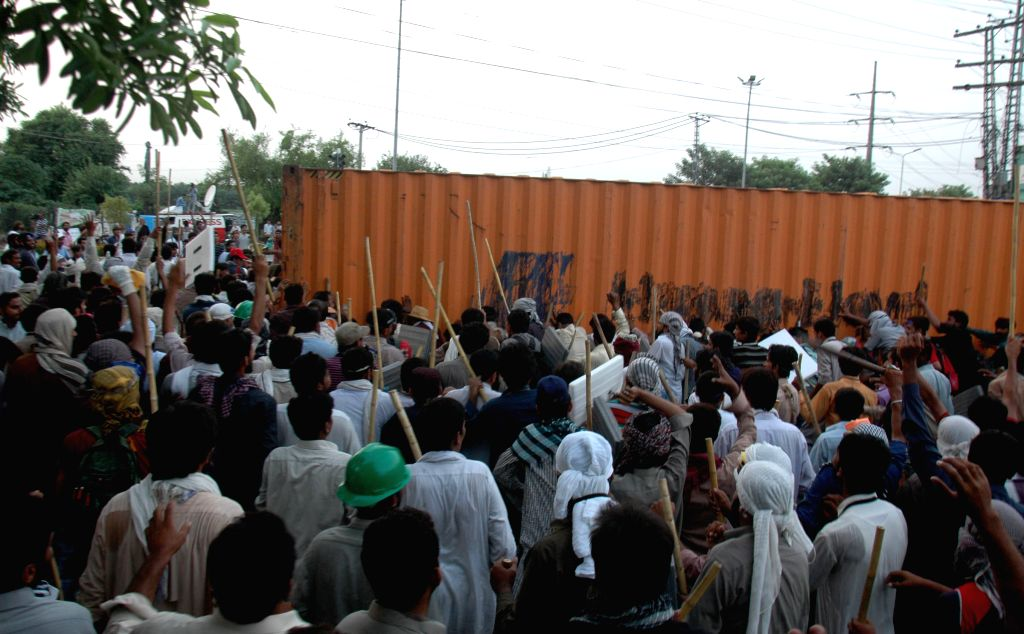 Protestors try to remove a container in eastern Pakistan's Lahore, on Aug. 8, 2014. Pakistan police used tear gas shells to disperse anti-government protesters in ...