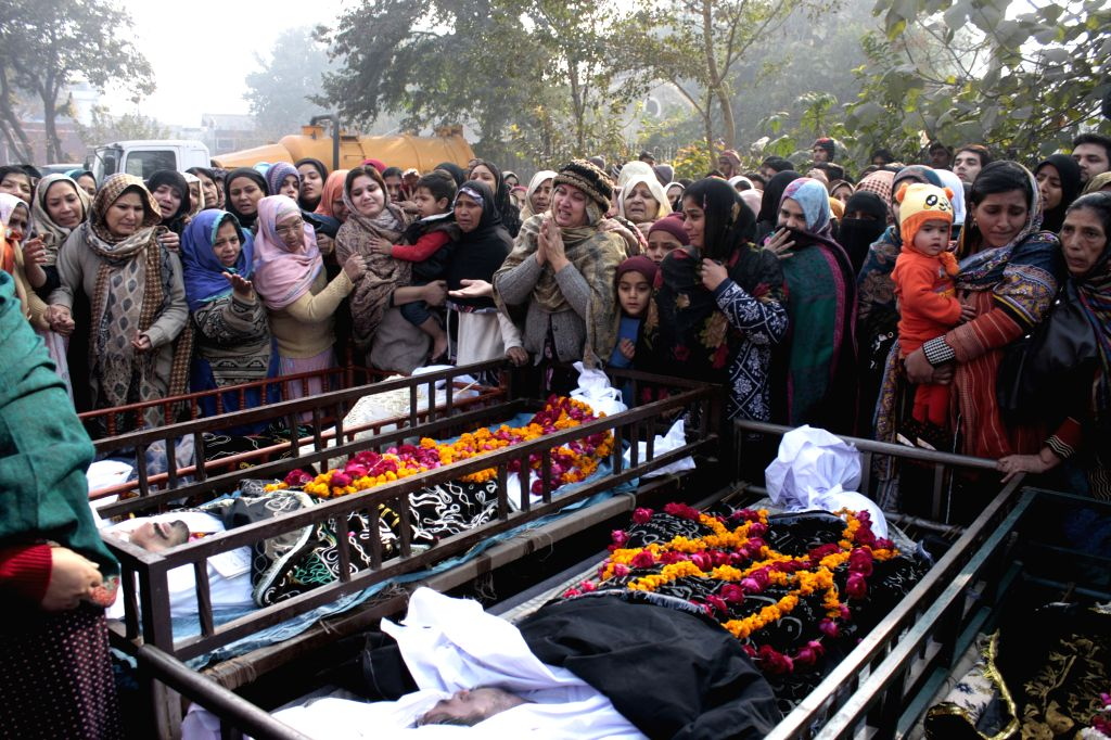 Mourners attend a funeral ceremony of victims of a fire in a four-story shopping plaza in east Pakistan's Lahore, on Dec. 30, 2014. At least 13 people were killed ...