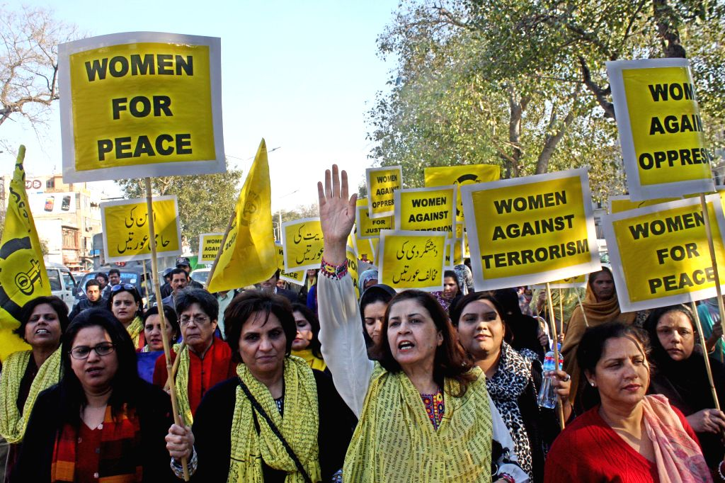 LAHORE, Feb. 12, 2014 (Xinhua) -- Pakistani women hold placards during a protest rally against terrorism in eastern Pakistan's Lahore on Feb. 12, 2014. At least 10 people were killed when some unknown militants stormed the house of a local peace mili