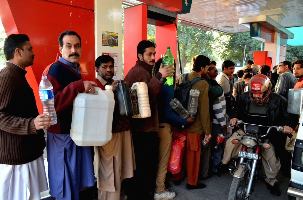 Pakistani people hold bottles at a petrol station in eastern Pakistan's Lahore on Jan. 17, 2015.  Delayed oil consignments have left large areas of the country ...