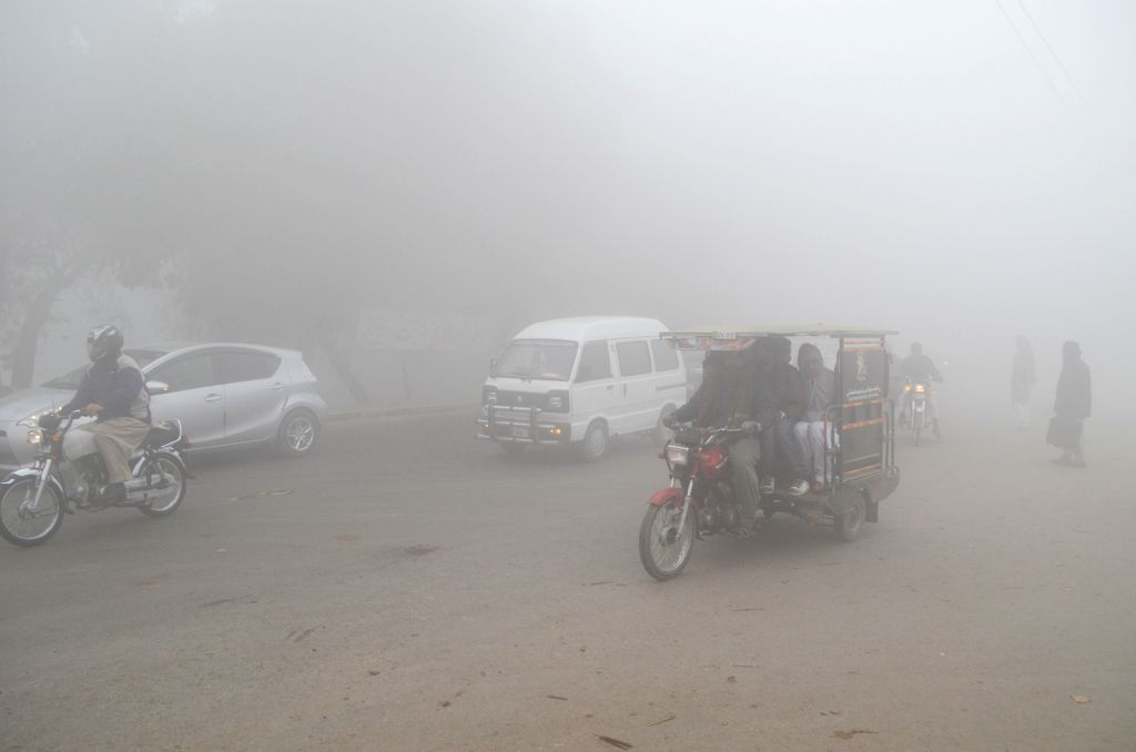 LAHORE, Jan. 24, 2019 - Vehicles move on a road in dense fog in Lahore, east Pakistan, Jan. 24, 2019. Lahore and its surrounding areas were completely blanketed by dense fog on Thursday, minimizing ...