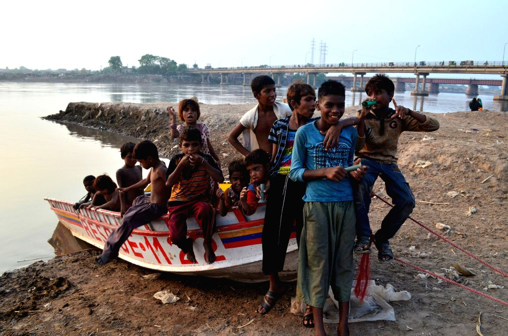 LAHORE, July 11, 2016 - Pakistani children sit on a boat at the bank of Ravi river in eastern Pakistan's Lahore on July 11, 2016.