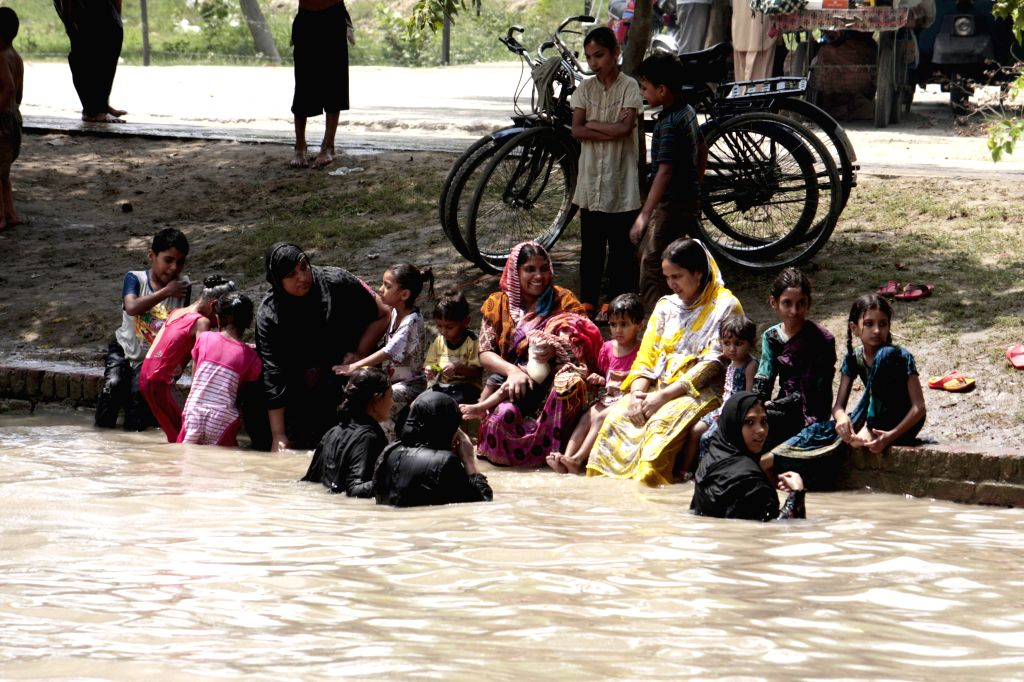 Pakistanis play in a canal during a hot day in east Pakistan's Lahore on July 15, 2014. Temperatures reach over 45 degrees Celsius in many parts of the country. ...