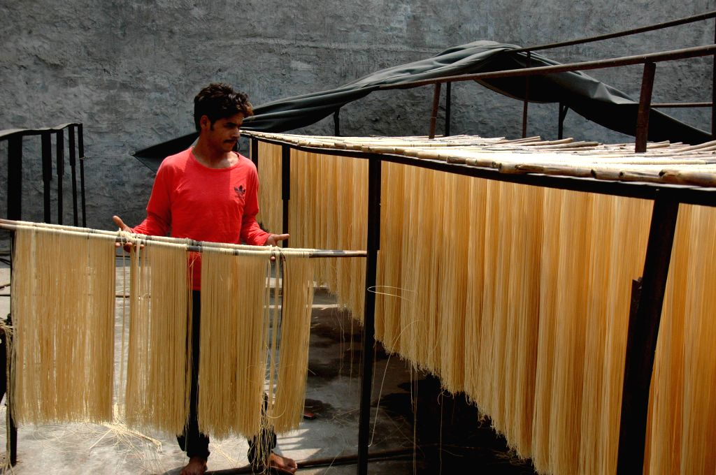 A man carries dried noodles at a local factory in east Pakistan's Lahore on July 16, 2014. Many Pakistani people buy noodles for an early morning meal before they ...