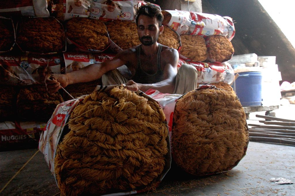 A man packs dried noodles at a local factory in eastern Pakistan's Lahore on July 16, 2014. Many Pakistani people buy noodles for an early morning meal before they ..