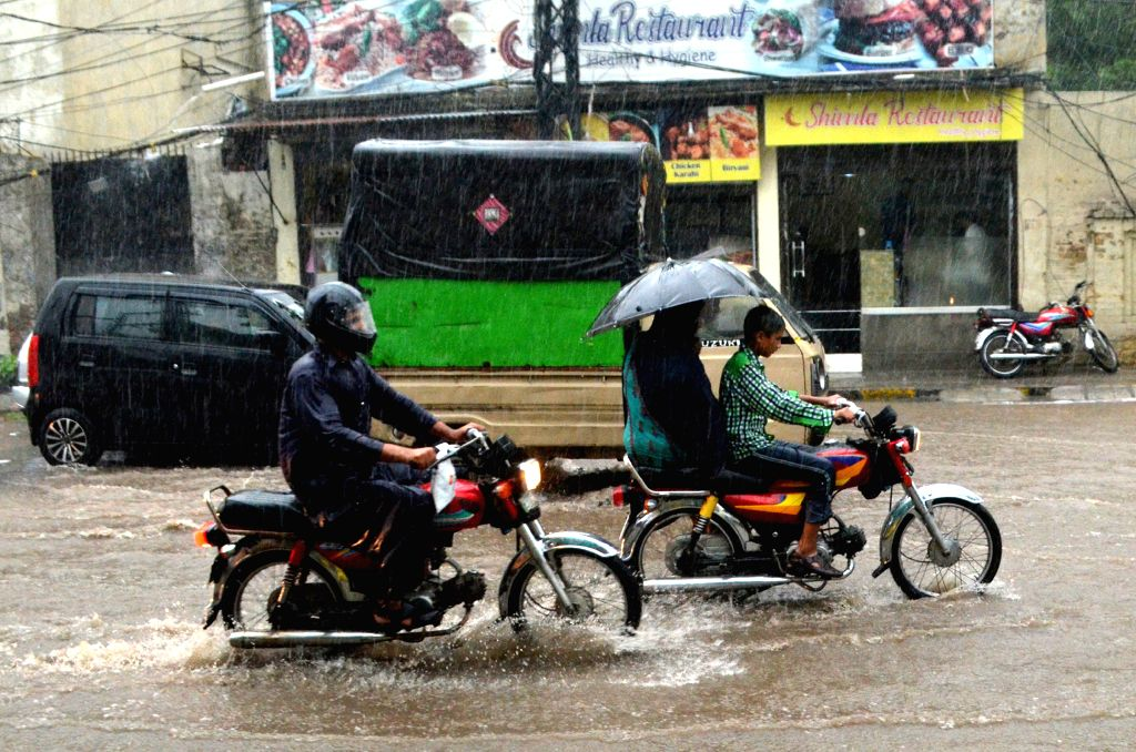 LAHORE, July 16, 2019 - Motorcyclists ride during heavy monsoon rain in eastern Pakistan's Lahore, on July 16, 2019.
